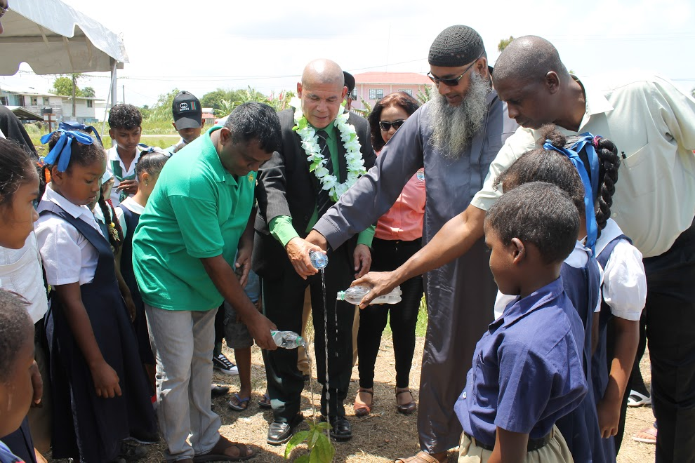 Minister of Social Cohesion, Dr. George Norton helping to water one of the newly planted trees