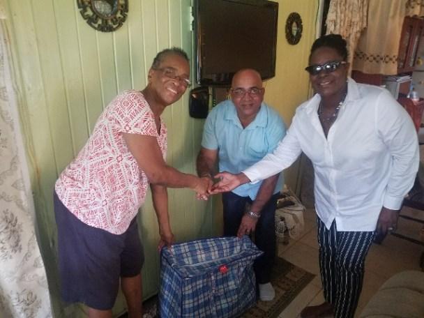 REO Denis Jaikaran and DREO Jennifer Ferreira-Dougall, donating a hamper to Myrtle Caldera.