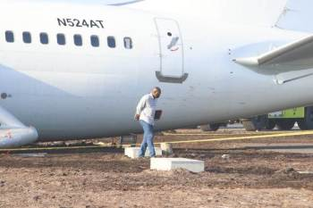Minister David Patterson inspects the site where the Fly Jamaica came to a standstill after the emergency landing.