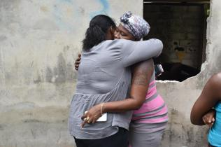 Minister Broomes consoles Natasha Cadogan who lost her home to a fire
