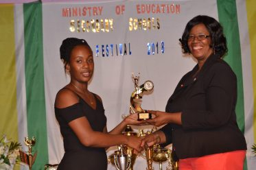 Teacher of Uitvlugt Secondary, Candacie Whaul-Amsterdam, receiving her award for Best Director from Administrator (ag) of the Unit of Allied Arts, Lorraine Barker-King