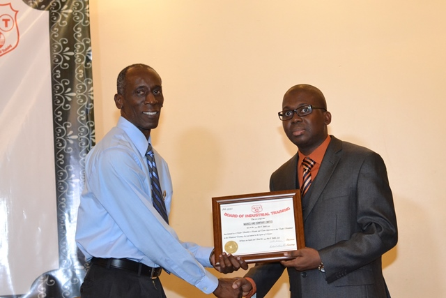 Representative from Marics and Company Limited accepting credentials for becoming a Master, from Chief Executive Officer of the Board of Industrial Training (BIT), Richard Maughn.