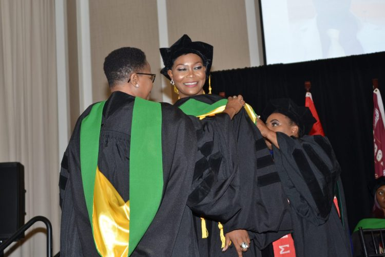 Valedictorian, Dr. Isioma Oside of Nigeria being conferred with a sash signifying her acquisition of a Degree in Medicine