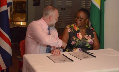 National Hydrographer of the UK Hydrographic Office, Rear Admiral Tim Lowe and Director General of the Maritime Administration Department, Claudette Rogers during the signing of the agreement