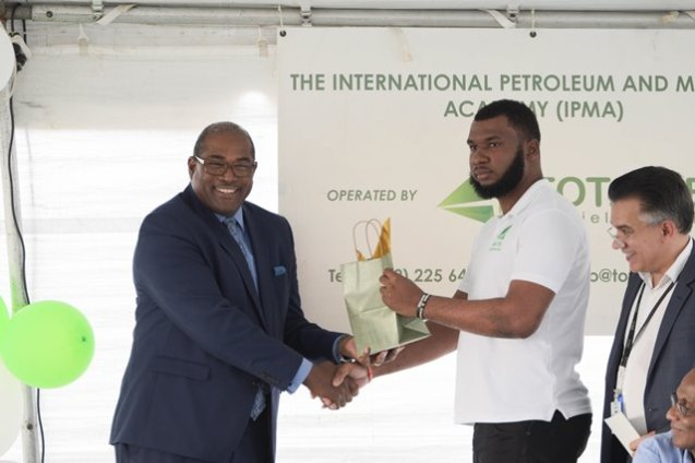 Top performer, Terrence Cave presents guest speaker, Nigel Huge with a special recognition on behalf of the patron of the Academy, Minister Raphael Trotman.