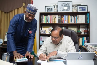 Prime Minister, Moses Nagamootoo autographs one of his books he presented to Minister of State Aviation, Federal Republic of Nigeria, Senator Hadi Sirika.