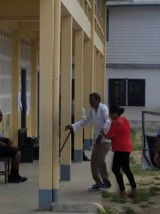 71-year-old Drupat Dalgoo being assisted into the polling place at Cotton Tree Primary, WCB.