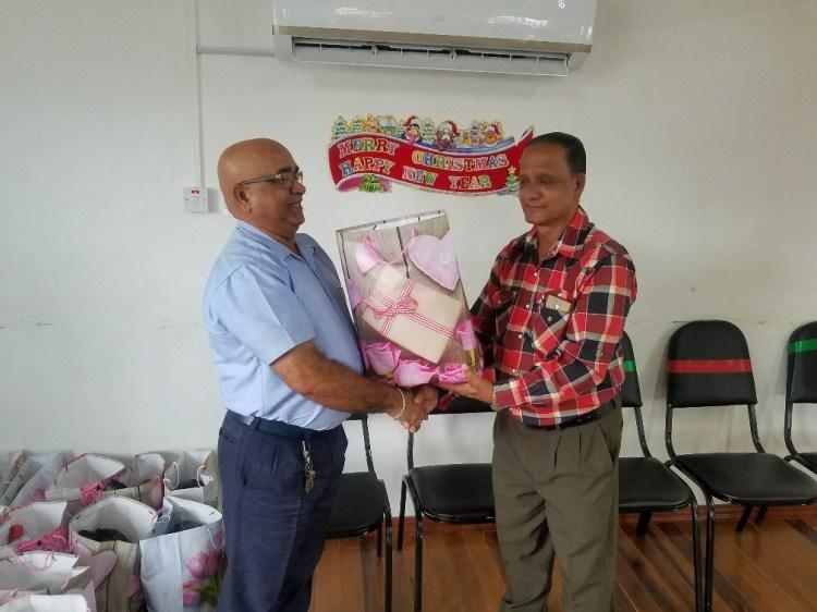Outgoing REO Denis Jaikaran presents a Christmas hamper to Regional Chairman Julius Faerber