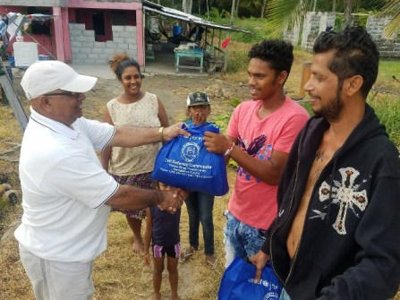 REO Denis Jaikaran presents a family a hamper of cleaning agents.