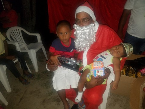 Santa Claus take time out from sharing gifts to take a photo with two little ones