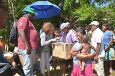 Minister within the Ministry of Indigenous Peoples' Affairs Valerie Garrido-Lowe along with Major Seam Welcome distributing hampers to the families