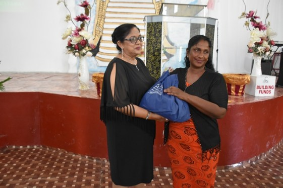 Hampers being presented by Mrs Nagamootoo to members of the congregation.