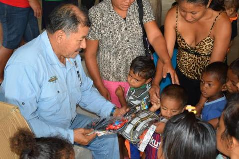 Minister of Indigenous Peoples' Affairs, Sydney Allicock distributing toys at Annai, Village, Region Nine.