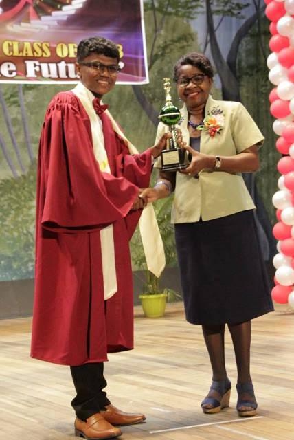 Valedictorian, Mr. Shurlun Tudor receiving one of his prizes from Director of NCERD, Mrs. Jennifer Cumberbatch.