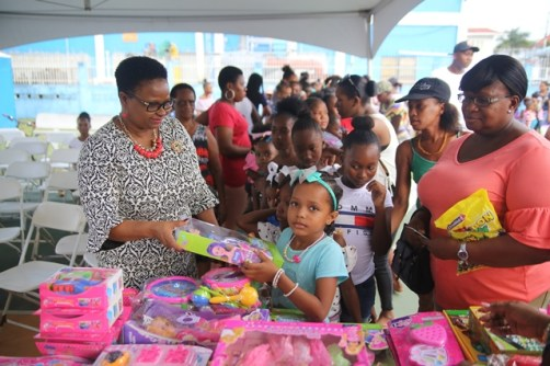 Minister of Public Health, Volda Lawrence distributing gifts to the children.