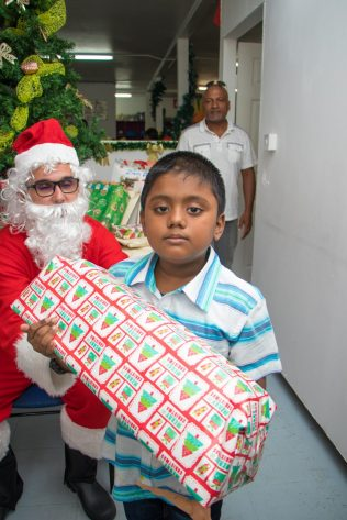 Another child receiving his gift from Santa Claus