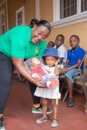 Minister Broomes gives a little one her early Christmas treat.