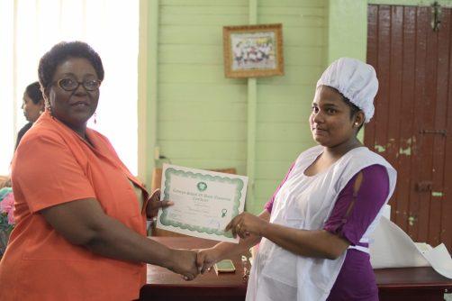 Emrita Seepaul receiving her certificates from Myrna Lee, Principal of the Carnegie School of Economics