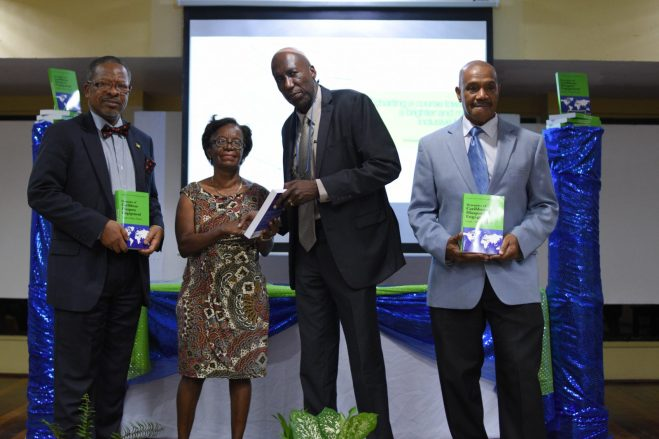 (left -right) Vice-Chancellor of the University of Guyana, Professor Ivelaw Griffith, a representative of the university's library receiving a copy of the book from Dr. Fitzgerald Yaw and (extreme right) Professor of Sociology University of North Georgia George Danns