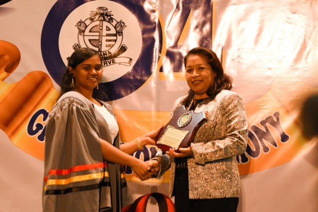 Minister of Public Affairs, Dawn-Hastings Williams presenting a plaque to overall best Graduating student, Annamarie Isserdeen Samaroo.