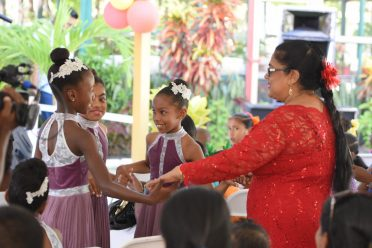 Mrs. Sita Nagamootoo shares a playful dance with some of the children