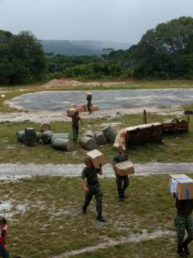Members of the Guyana Defence Force transporting the hampers from the airstrip to the community.