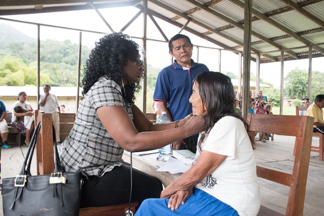 Waipa's Toshao looks on as Dr. Kay Shako examines one of the residents who accessed services at the medical outreach.