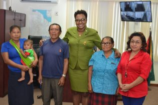 Minister within the Ministry of Public Infrastructure, Annette Ferguson flanked by residents of Chinoweng, Region seven
