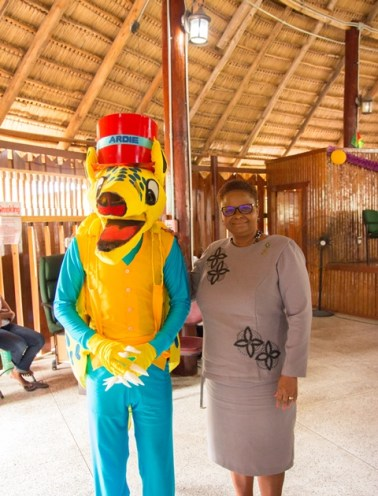Minister of Public Health, Volda Lawrence shares a light moment with the Armadillo mascot.