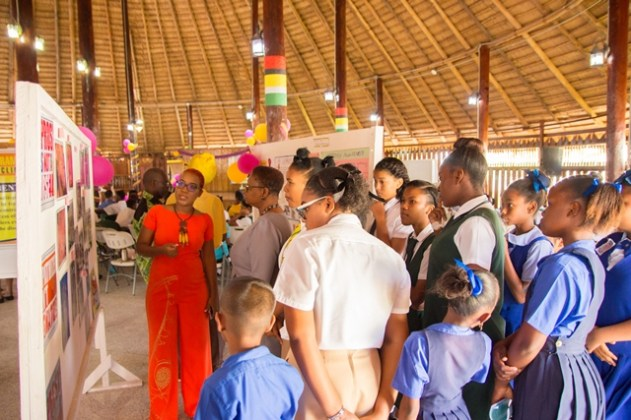 Minister of Public Health Volda Lawrence viewing the exhibition with students from various schools.