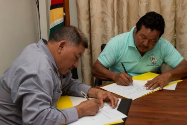 Minister of Indigenous Peoples' Affairs Sydney Allicock and Amerindian Peoples Association (APA), President, Mario Hastings signing the MOU.