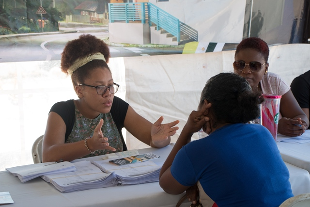 A Community Development Officer explaining the application process to an applicant at the Kitty Market outreach.