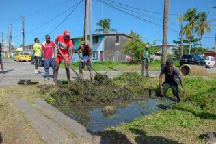 Young people in the community of West Ruimveldt clearing a drain during a clean-up exercise.
