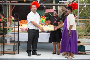 An official from the Chinese Association of Guyana making the donation to the Winsor Forest Primary School.