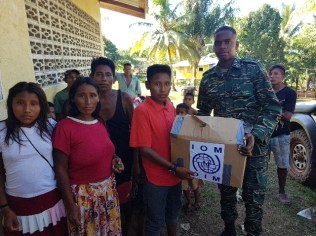 The Civil Defence Commission (CDC) hands over a hamper to a migrant family in Khan's Hill, Region 1.