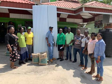Minister within the Ministry of Communities with responsibility for Housing, Valarie Adams- Yearwood [centre], making the presentation of the zinc sheets and cement to Oscar Anthony [immediate left] and Roslyn Gordon [second left