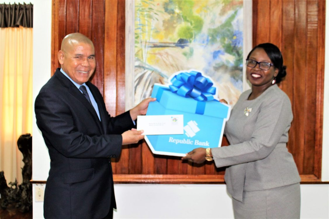 Minister Norton accepts both the symbolic and real cheque from Republic Bank's Assistant Communications and Public Relations Officer, Ms. Jonelle Dummett