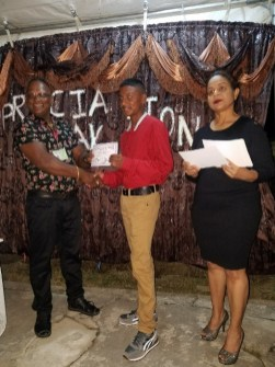 Chairman of the Parika Facade CDC, Sunil Oudit handing out a certificate to a volunteer. Also, in photo Technical Officer at the Department of Social Cohesion, Pamela Nauth.