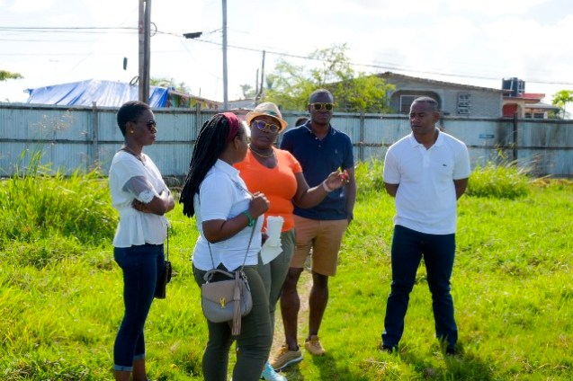 Minister Broomes (second from left) and some of the other officials involved in the clean up initiative engaged in discussion.