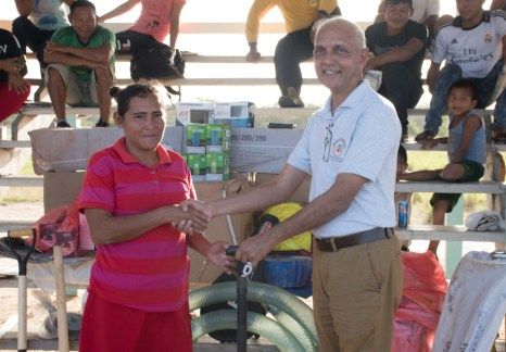 Minister Bulkan hands over some of the farming equipment to one of the residents
