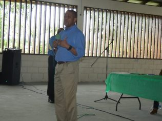 Director of the Department of Energy, Dr. Mark Bynoe addresses the youth of Linden