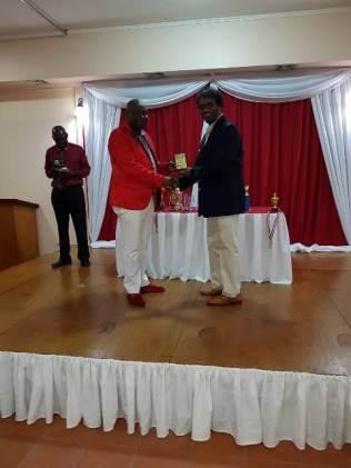 Businessman Halim Khan receiving his award from Commander Edmond Cooper.