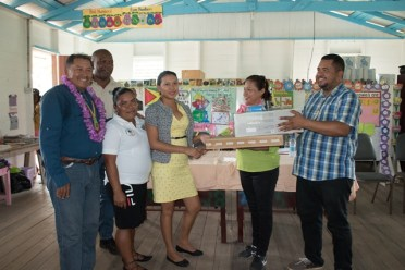 Minister of Indigenous Peoples' Affairs, Sydney Allicock and Minister of Public Affairs, Dawn Hastings-Williams handing over a computer and printer to Teacher of the Mabura Primary School, Shevonne Williams in the presence of Senior Administrator, National Data Management Authority (NDMA), Marlon Pearson and Toshao of Great Falls, Nicole Daniels.
