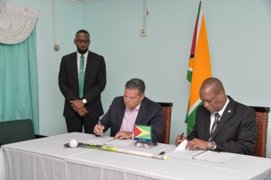 Minister of State, Mr. Joseph Harmon and President of the Guyana Hockey Board, Mr. Philip Fernandes sign the Memorandum of Understating for the construction of a state of the art Hockey facility as Director of Sport, Mr. Christopher Jones looks on.
