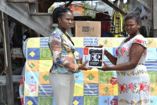 Ministry of Social Protection, Technical Officer, Sonia Philander presents Caroline Sasnarine with a stove.