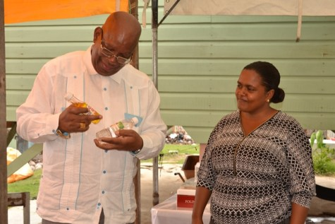 Minister of Finance, Winston Jordan inspects a bottle of carrot oil as Hafeeza Smith looks on.