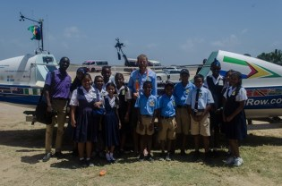 Commonwealth Rower, Richard Allen poses for a quick picture with students of Providence Primary School.