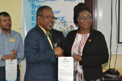 Vice-Chancellor of the University of Guyana, Professor Ivelaw Griffith presents a Certificate of Appointment to one of the Board Members.