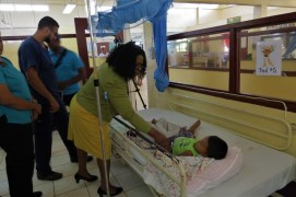 Dr Karen Cummings, Minister within the Ministry of Public Health interacts with a patient in the Pediatrics ward during her recent visit to the Mabaruma Regional Hospital.