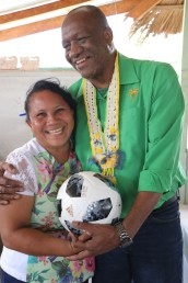 Minister of State, Joseph Harmon presents a resident of Achiwib with one of the footballs from among the sports gear donated to the village